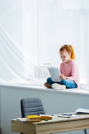 adorable child using digital tablet while sitting on windowsill