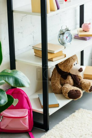 books, alarm clock and teddy bear on shelves and pink school bag on carpet