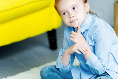cropped shot of pensive little child looking away at home