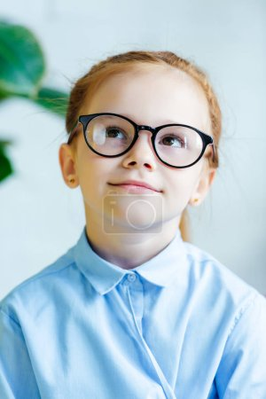 portrait of beautiful little redhead child in eyeglasses smiling and looking up