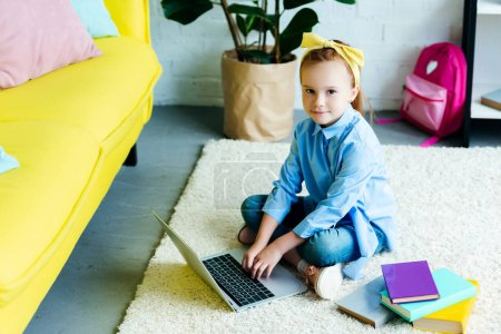 high angle view of beautiful child using laptop and looking at camera at home