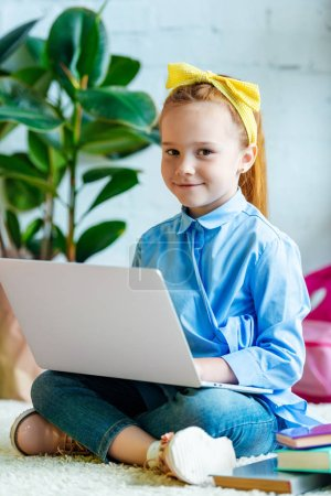 cute little child using laptop and smiling at camera