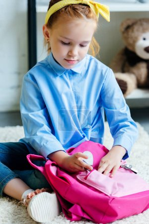 adorable child packing pink school bag at home