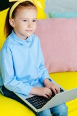 adorable little redhead child sitting and using laptop
