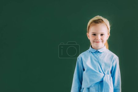 Photo for Adorable little redhead schoolgirl standing near blackboard and smiling at camera - Royalty Free Image