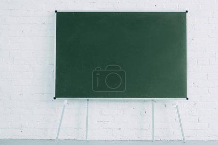 blank blackboard and white brick wall