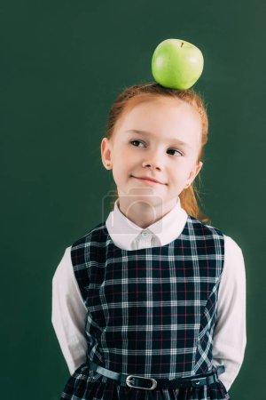 smiling pensive little schoolgirl with apple on head looking away