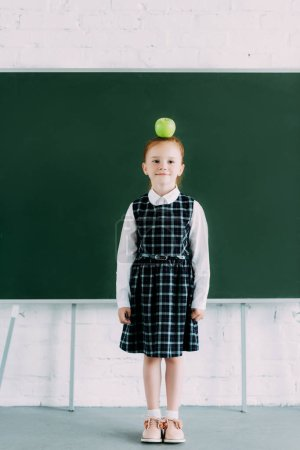 full length view of beautiful little redhead schoolgirl with apple on head looking at camera