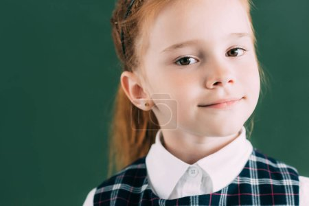 close-up portrait of beautiful little redhead schoolgirl looking at camera
