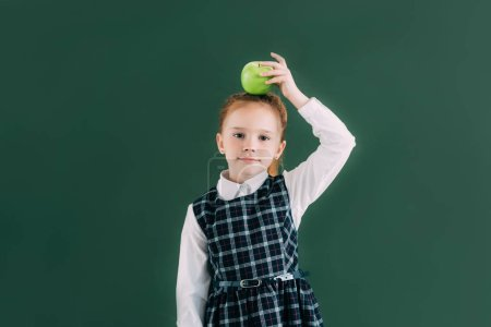 beautiful little red haired schoolgirl with apple on head looking at camera