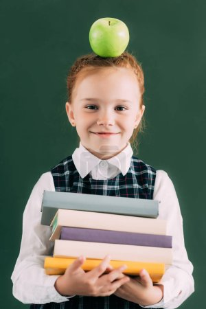 adorable little redhead schoolgirl with apple on head holding pile of books and smiling at camera