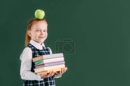 belle petite écolière avec pomme sur la tête tenant pile de livres et souriant à la caméra
