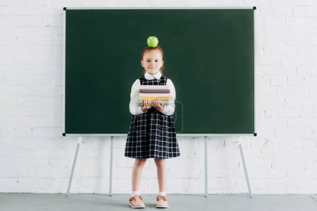 cute little schoolgirl with apple on head holding pile of books and looking at camera while standing near blackboard