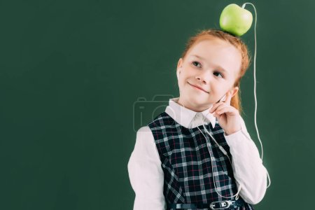 Photo for Adorable pensive schoolgirl with apple on head and earphones smiling and looking away - Royalty Free Image
