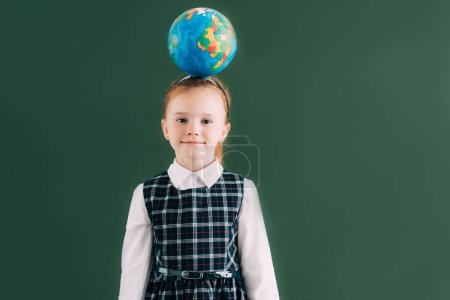 adorable little schoolgirl with globe on head standing near blackboard and smiling at camera