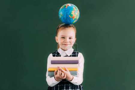 little redhead schoolgirl with globe on head holding pile of books and smiling at camera