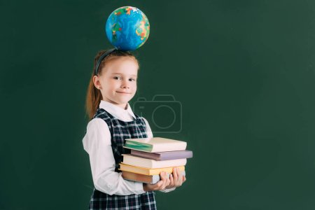 beautiful little schoolgirl with globe on head holding pile of books and smiling at camera