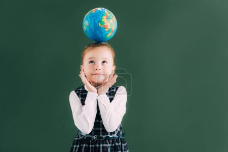 adorable little red haired schoolgirl with globe on head looking up while standing near blackboard