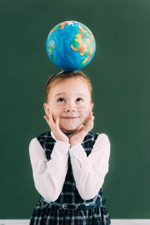 cute smiling schoolgirl with globe on head looking up while standing near chalkboard