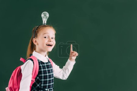 adorable happy schoolchild with backpack and light bulb on head pointing up with finger and smiling at camera