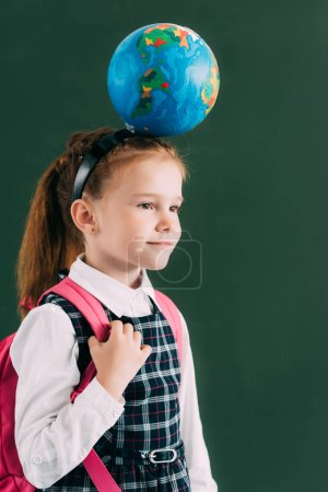 adorable little schoolgirl with backpack and globe on head looking away