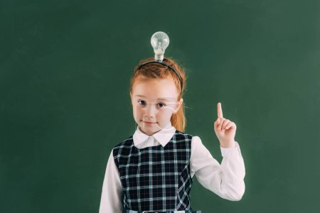 adorable little redhead schoolgirl with light bulb on head pointing up with finger and looking at camera