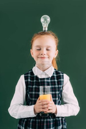 happy little schoolgirl with closed eyes and light bulb on head holding glass of orange juice