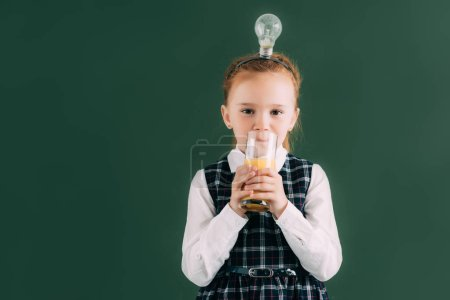 adorable little schoolgirl with light bulb on head drinking juice and looking at camera