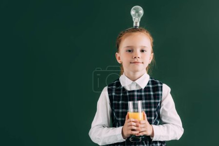 adorable little schoolgirl with light bulb on head holding glass of juice and smiling at camera