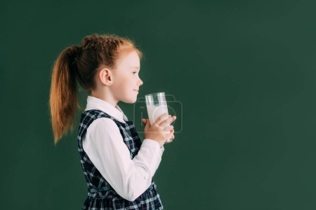 side view of smiling little schoolgirl holding glass of milk while standing near chalkboard