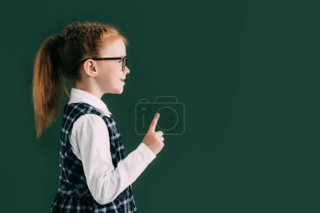 side view of little smiling schoolgirl in eyeglasses pointing with finger while standing near blackboard