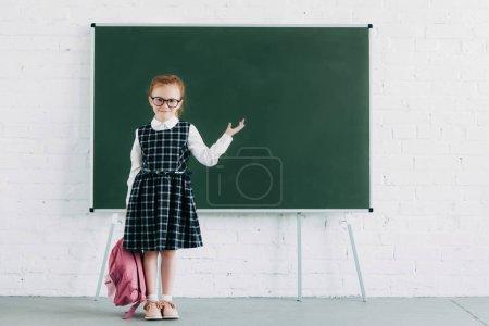 Photo pour Adorable petite écolière avec sac à dos montrant tableau noir vierge et souriant à la caméra - image libre de droit