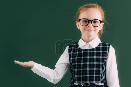 adorable little schoolgirl in eyeglasses showing blank chalkboard and smiling at camera