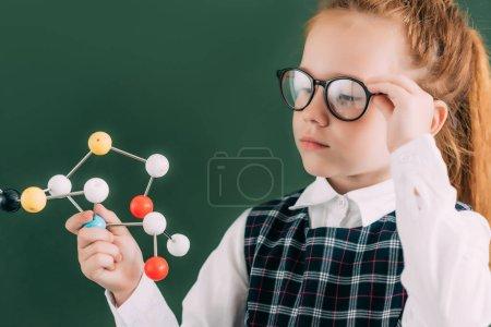 beautiful little schoolgirl in eyeglasses holding molecular model while standing near chalkboard