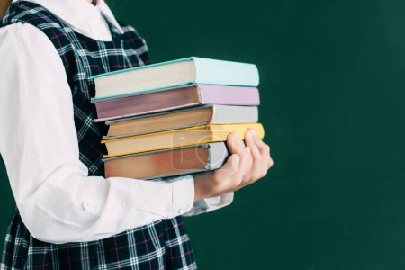 cropped shot of schoolgirl holding pile of books while standing near blackboard