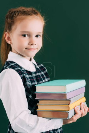 adorable little schoolgirl holding pile of books and smiling at camera