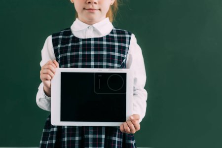 cropped shot of cute little schoolgirl holding digital tablet with blank screen