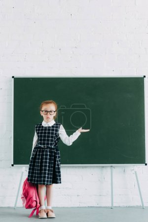 adorale little schoolgirl in eyeglasses holding pink school bag and showing blank chalkboard