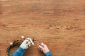 cropped image of man with prosthetic arm cutting wires by nippers at wooden table