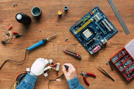 Foto de Recortar imagen de hombre con brazo prostético reparar cables destornillador en mesa de madera - Imagen libre de derechos