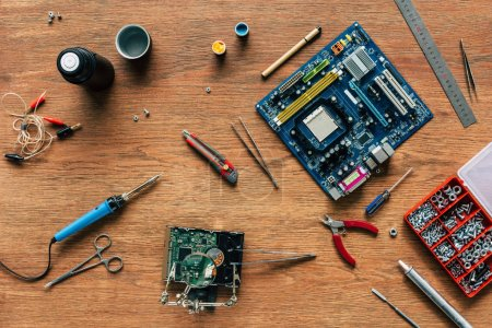 top view of repairing tools, motherboard and hard drive on wooden table