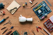 top view of prosthetic arm doing thumb up gesturing on table with tools