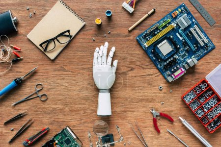 Photo for Top view of prosthetic arm on wooden table with tools, spectacles and textbook - Royalty Free Image