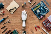 top view of prosthetic arm on wooden table with tools, spectacles and textbook