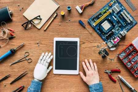 cropped image of  electronic engineer with robotic hand sittng at table with digital tablet surrounded by tools