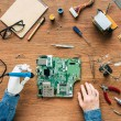 cropped image of electronic engineer with robotic hand fixing motherboard by soldering iron at table surrounded by tools