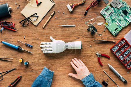 cropped image of man with amputee sitting at table with prosthetic arm surrounded by tools