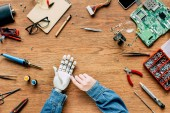 cropped image of man fixing robotic hand by screwdriver at wooden table