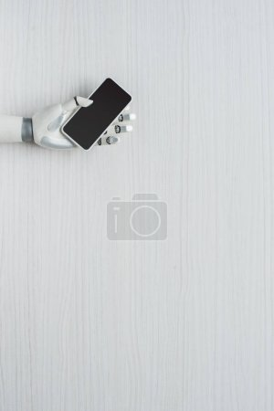 Photo for Partial view of prosthetic arm holding smartphone with blank screen - Royalty Free Image
