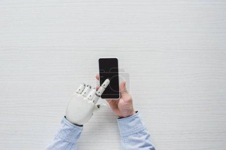 Photo pour Image recadrée de l'homme avec main cyborg en utilisant un smartphone avec écran blanc sur table en bois - image libre de droit